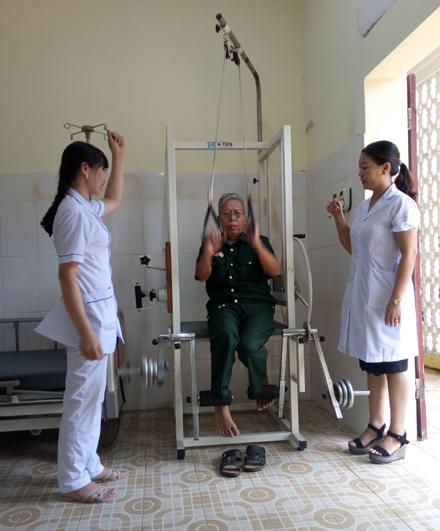 Bác sĩ Phạm Thị Hoa (phải) cùng điều dưỡng hướng dẫn thương binh tập phục hồi.